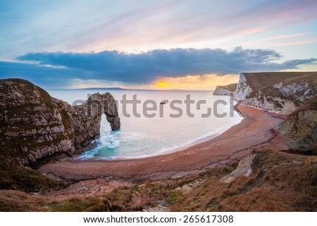 Sunset at Durdle Door natural limestone arch on the Jurassic Coast near Lulworth in Dorset England UK Europe - stock photo