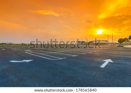 Sunset at empty parking lot - stock photo