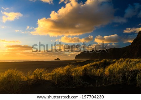 Sunset at Karekare Beach, Auckland Region, New Zealand - stock photo