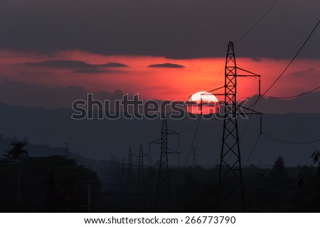 sunset at mountain range and  High voltage electricity pylon background - stock photo