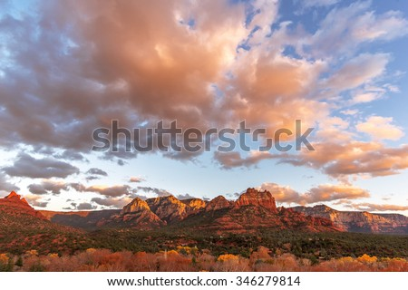 Sunset at Oak Creek Canyon in downtown Sedona, Arizona. In the background geological features, red mesas and buttes, with beautiful blue skies, with white clouds. - stock photo