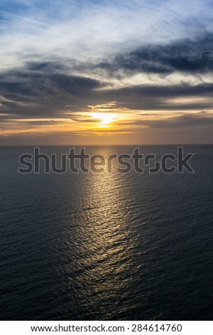 sunset at ocean with cloudy scene
