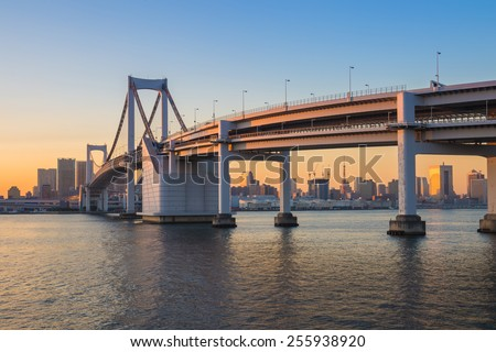 Sunset at Rainbow bridge with Tokyo tower in background - stock photo