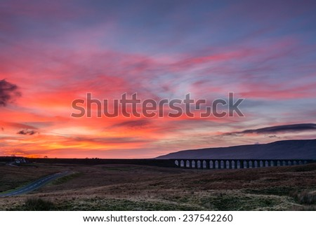 Sunset at Ribblehead Viaduct / The Ribblehead Viaduct carries the Settle to Carlisle Railway across Batty Moss spanning 400 m and 32 m above the valley floor - stock photo