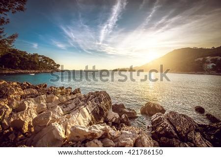 Sunset at rocky stone beach at Korcula island in Croatia. Adriatic sea. - stock photo