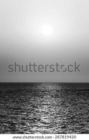 sunset at sea black and white - stock photo