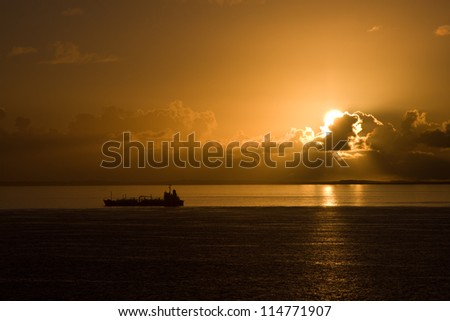 Sunset at sea with cargo ships in the background
