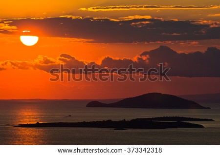 Sunset at sea, with small greek islands in background, Sithonia, Greece - stock photo