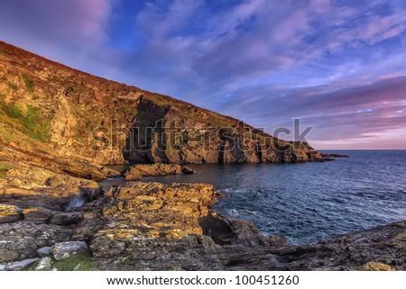 Sunset at Silver Cove overlooking the Mewstone, Wembury, Devon, UK - stock photo