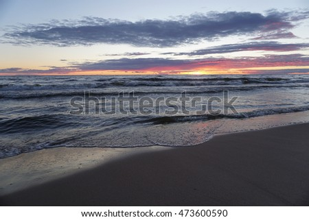 Sunset at the beach with waves on shore
