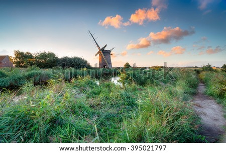 Sunset at the beautiful ruins of Brograve Windmill on the banks of a narrow stretch of water known as the Waxham New Cut