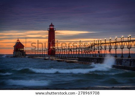 Sunset at the Grand Haven South Pierhead Inner Light with Entrance Light in background in Grand Haven State Park in Grand Haven, Michigan - stock photo