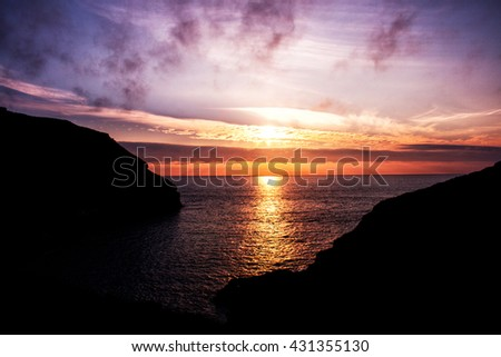 Sunset at the headland at Tintagel castle in Cornwall, England on a cloudy summer day. King`s Arthur castle ruins.  - stock photo