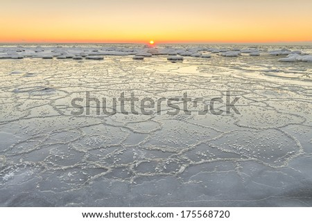 Sunset at the icy beach - stock photo