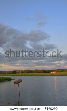 sunset at the pond with duck nest - stock photo