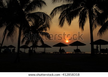 Sunset at the seafront in a tropic jungle, fringed by coconut trees swaying in the sea breeze and lined with gazebos. - stock photo