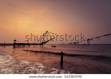 Sunset at tropical beach. Ocean coast landscape with chinese fishing nets silhouette at Cochin (Kochi). South India, Kerala, Kochin - stock photo