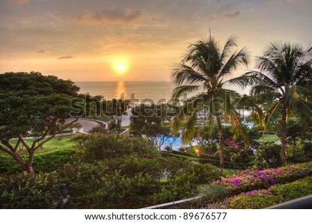 Sunset at tropical resort with view of ocean and lush garden.