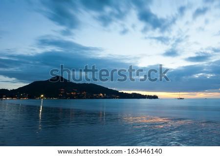 Sunset at tropical sandy beach. Sunset at tropical beach. Evening ocean landscape under dramatic stormy sky. Phuket, Thailand - stock photo