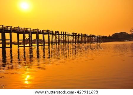 Sunset at U Bein Bridge in Mandalay , Myanmar - stock photo