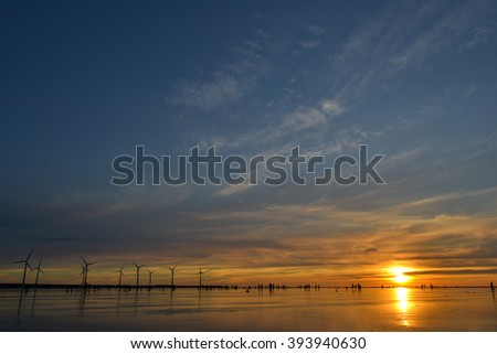 Sunset at wetland with wind generators - stock photo