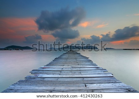 Sunset at wooden bridge on the sea with clouds moving in the sky background