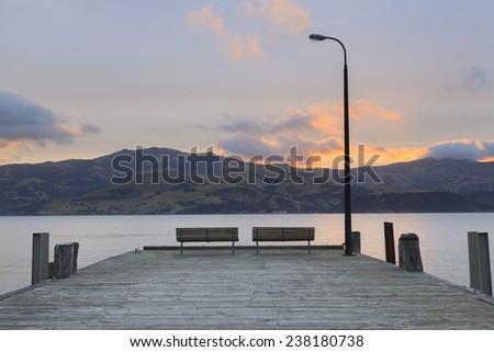 Sunset at Wooden pier in Akaroa, Canterbury region, South Island, New Zealand. - stock photo