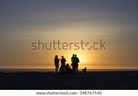 Sunset back light view of people on the beach