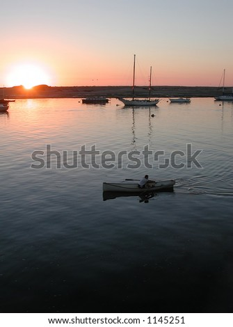 Sunset, bay, boats and paddler. - stock photo