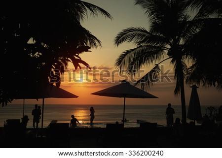 "Sunset, beach chairs, palm trees, infinity swimming pool silhouette. Bali ""dream land"" - stock photo"