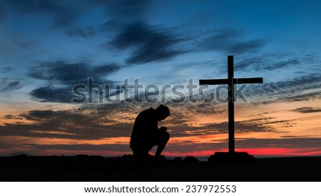 Sunset behind a man praying next to a cross on a hill