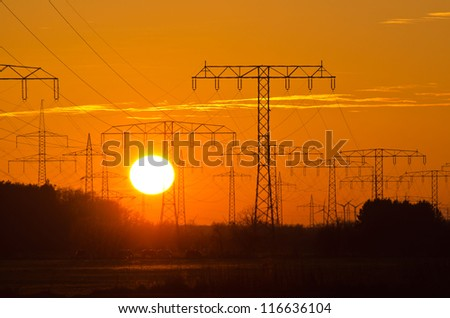 Sunset behind a power line - stock photo