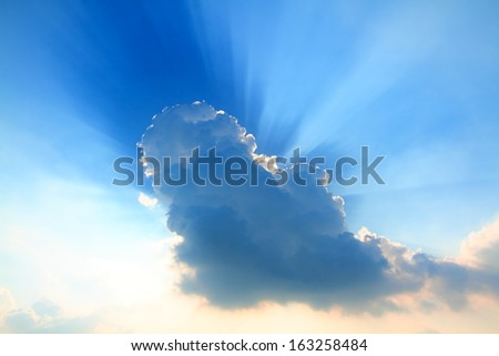 Sunset behind cloud with sun ray around - stock photo