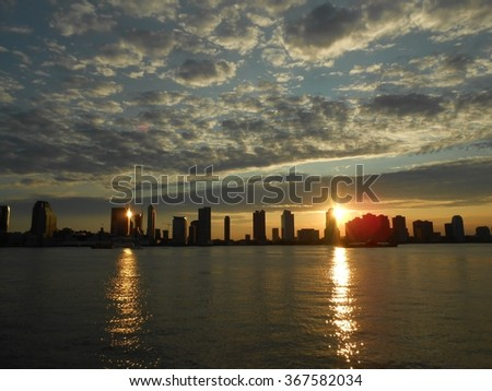 Sunset behind Jersey City, NJ - View from Battery Park in Manhattan, New York, NY. - stock photo