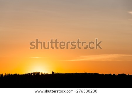 Sunset behind lake and forest - stock photo