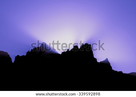 sunset behind mountain violet background - stock photo