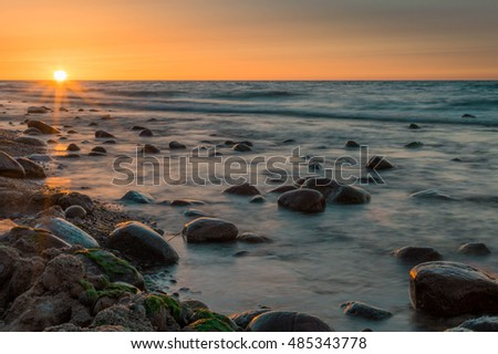 Sunset behind stones in a sea