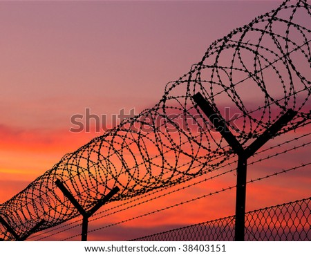 sunset behind the barbed wire - fence with red sky background - cd cover rear - stock photo