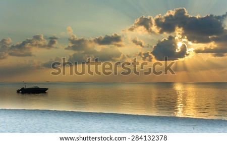 Sunset behind the clouds and a boat at the beach - stock photo