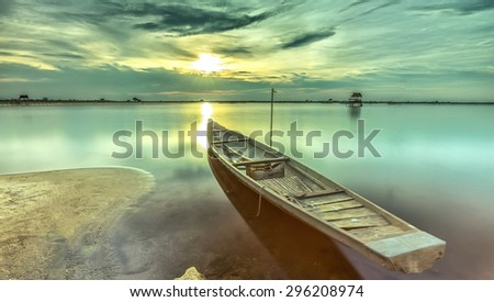 Sunset boat with the bow towards the sun is radiating rays  horizon pave the dive location. Smooth water surface gives very peaceful setting in the countryside Hue - stock photo