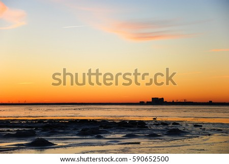 Sunset by the coast of the Baltic Sea with the skyline of the city Kalmar in the horizon