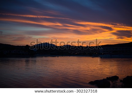 sunset cloudscape with orange and blue clouds over the coastline of Golfo Aranci, Sardinia,Italy - stock photo