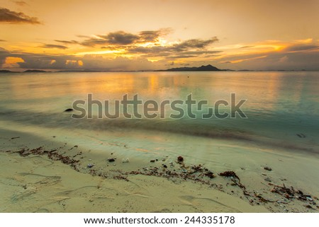 sunset colors in a deserted beach. - stock photo