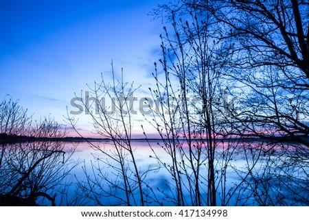 Sunset colors lightening up a lake behind trees. Saadjarv, Estonia - 05/MAY/2014 - stock photo