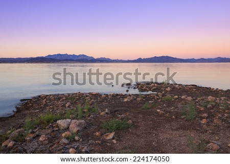 Sunset colors the skies and waters of Lake Mead at the Lake Mead National Recreation Area in Nevada, USA. - stock photo