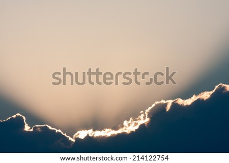 Sunset filtering through storm clouds. - stock photo