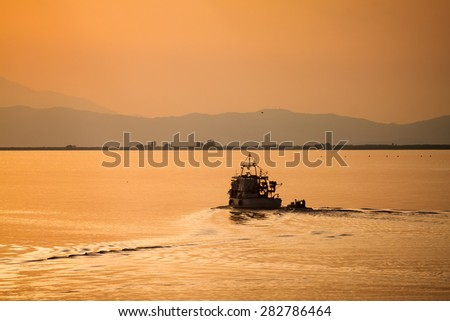 Sunset fishing boat in Thassos, Greece - stock photo