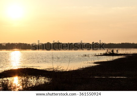 Sunset Fishing. Hudson Lake at sunset. View from shore of the lake with the sun low in the sky reflecting off of the water with a pair of recreational fishermen in the distance casting their lines. - stock photo