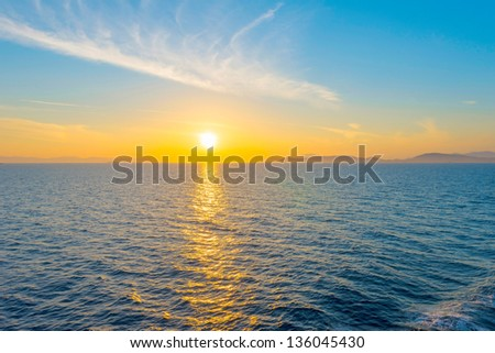 Sunset from ship at Mediterranean Sea during tour in Greece to Greek Islands - stock photo