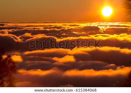 Sunset from the  top of mountain over the clouds